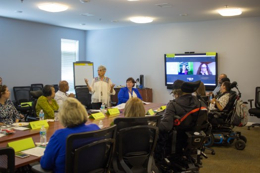 A group of people sit around a long wooden table. At the head of the table is a large screen showing two faces. Four of the people are using power wheelchairs, one woman stands and speaks to the group.