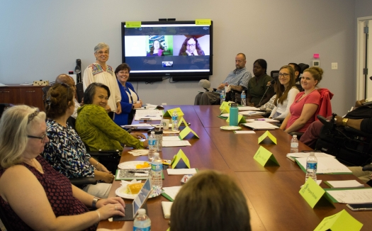 A group of people sit and stand around a large table in a conference room. On the wall at the head of the table is a screen with the faces of two women video conferencing in.