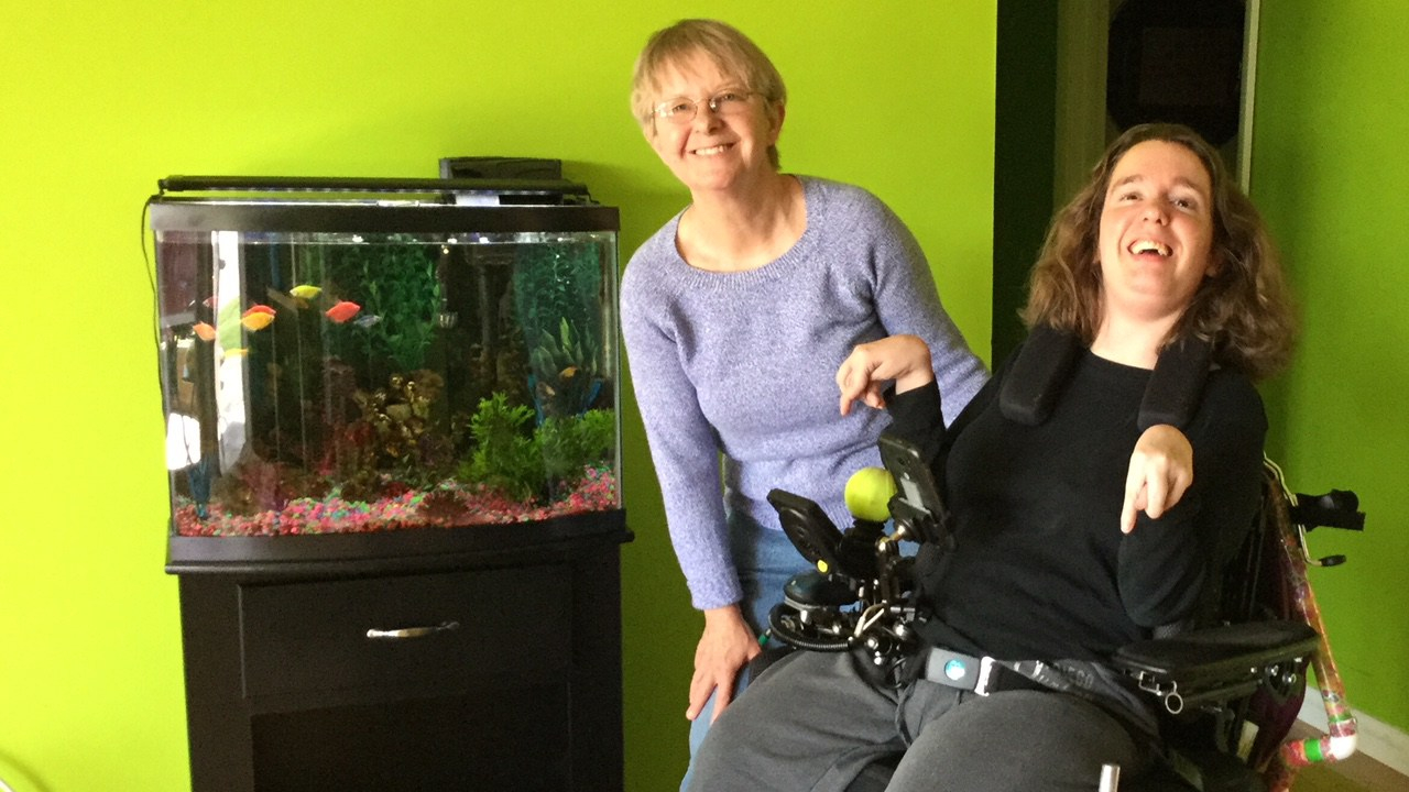 two women, one using a power wheelchair and fish tank.