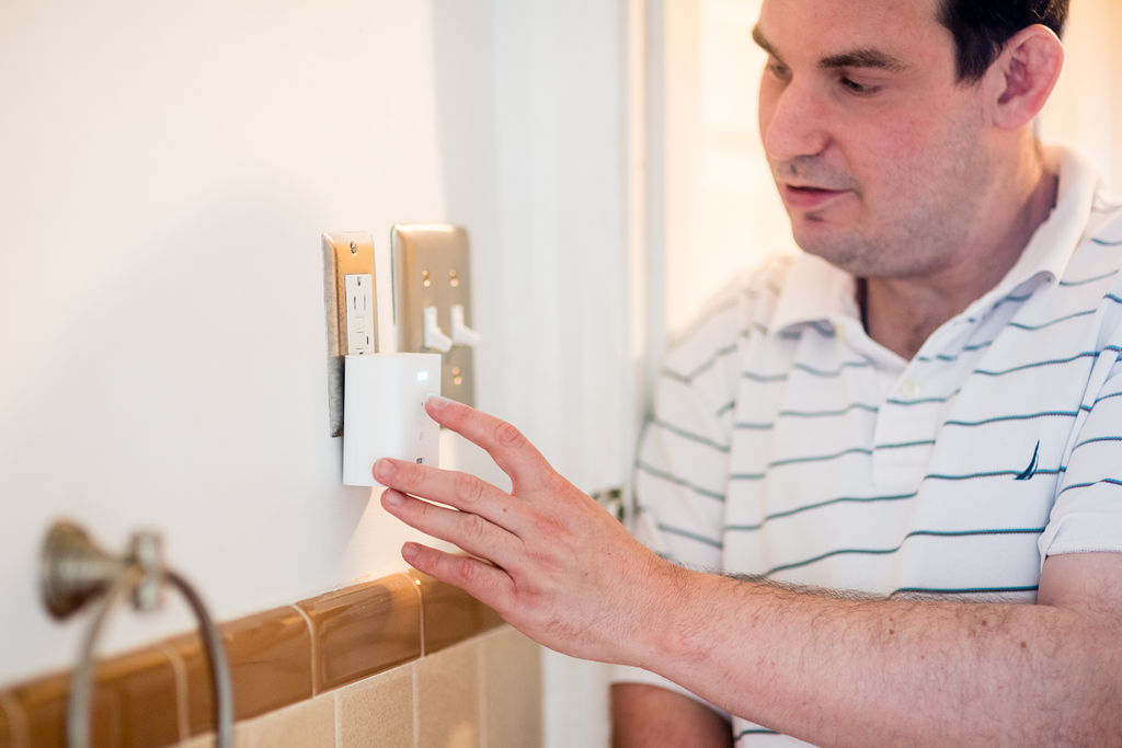A white man stands in the doorway of a bathroom and touches a device plugged into the wall outlet. He is wearing a collared white shirt with thin blue stripes. The device is a small white box about three inches long with a small white light on the top front.