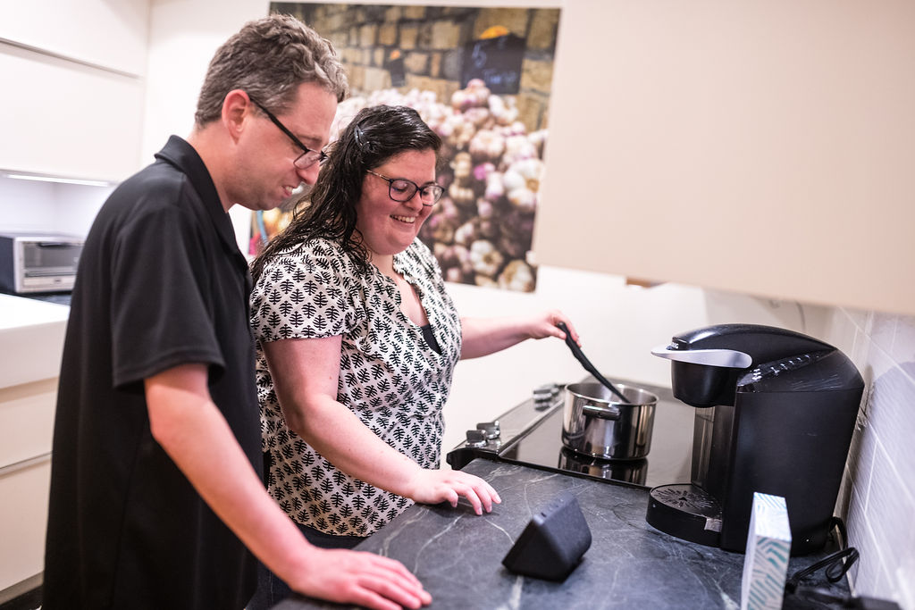 A young white man and woman cook in a brightly lit kitchen. They both wear glasses and he is wearing a collared black shirt and she is wearing a white blouse with a black check pattern. She stirs a pot on the stove. They are both smiling and looking at a smart display on the counter.