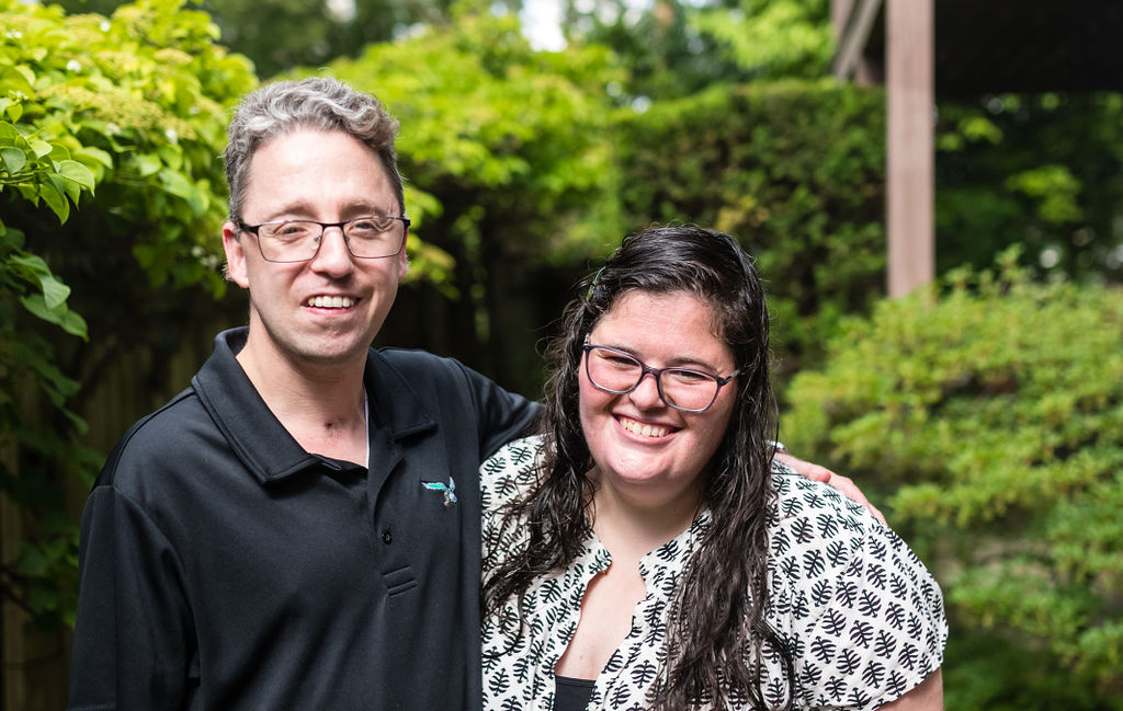 A young white man and woman stand outside in a green garden. They are smiling at the camera with their arms around each other. They both wear glasses and he is wearing a collared black shirt with the Philadelphia Eagles emblem on it and she is wearing a white blouse with a black check pattern.