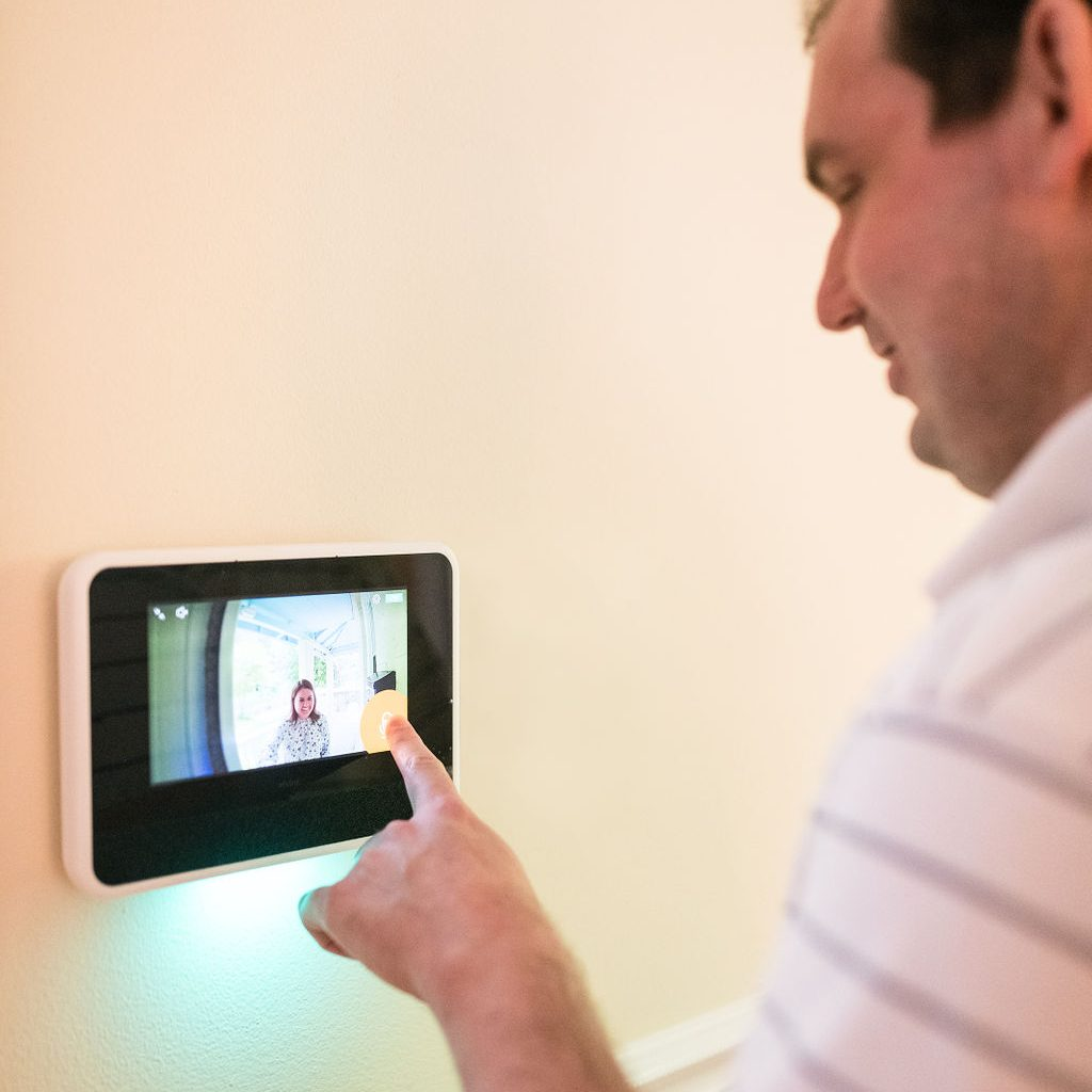 A white man taps a touch screen installed on a wall. The screen displays the view from his front doorbell, showing a woman smiling and standing outside.