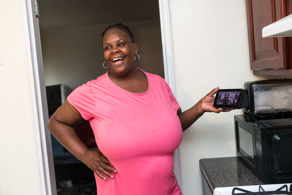 A black woman laughs and looks off camera with her hand on her hip while holding a smart display. She is wearing a pink short-sleeve dress and her hair is pulled back. She is standing in a kitchen.