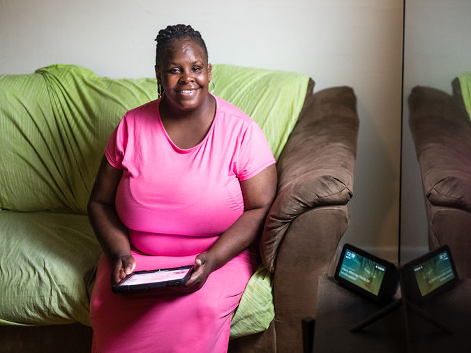 A black woman smiles and looks at the camera while holding a tablet. She is seated on a couch next to a table where a smart display rests. She is wearing a pink short-sleeve dress and her hair is braided and pulled back.