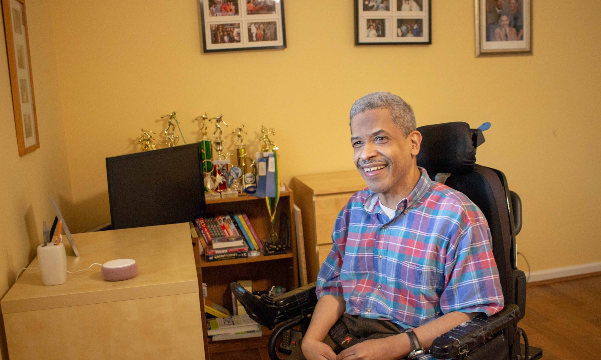 A black man smiles at the camera next to a desk where a smart speaker sits. The man is sitting in a power wheelchair with his hands in his lap. He has a mustache and greying hair, and he is wearing a plaid short-sleeved shirt. Behind him are shelves with a number of trophies and books and images of family and friends hang on the wall.