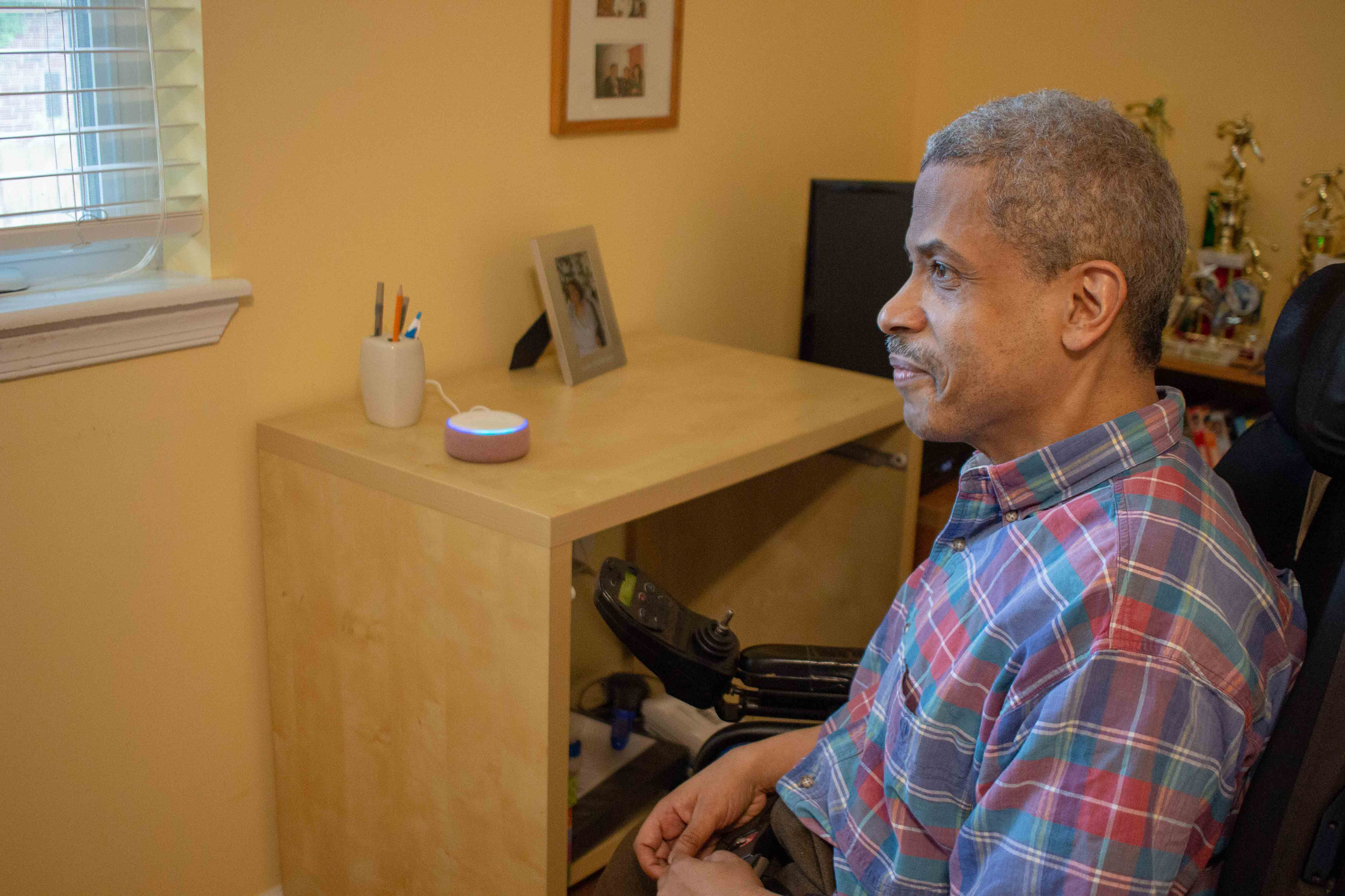 A black man sits in the foreground with a slight smile and stares off toward a window. Behind him on a desk is a smart speaker which has lit up. The man is seated in a power wheelchair with his hands in his lap. He has a mustache and greying hair, and he is wearing a plaid short-sleeved shirt.